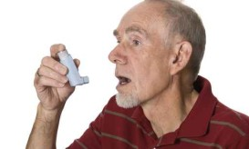 Senior man using asthma inhaler