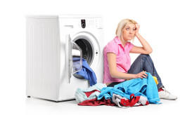 Thoughtful woman with clothes seated next to a washing machine