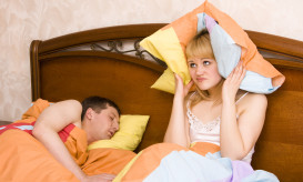 Woman awaking by her husband snoring