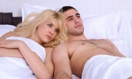 Young unhappy heterosexual couple in bedroom