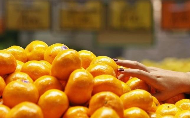A woman picks up some mandarin oranges at a fruits shop in Sydney