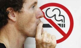 man smoking a no-smoking sign