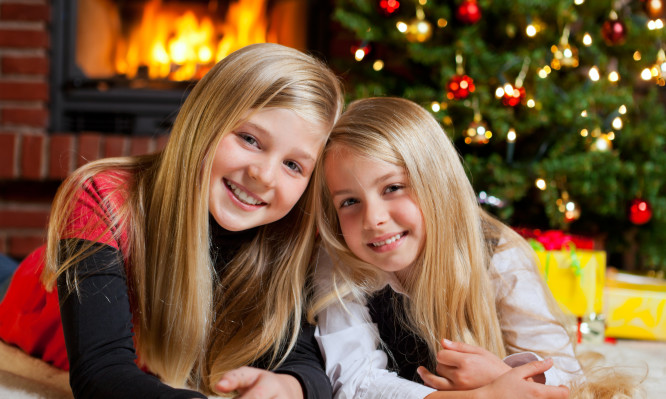 two girls on christmas eve tree and fire place in background