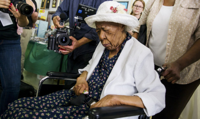 """Susannah Mushatt Jones (C), known as """"Miss Susie"""" is wheeled into a celebration for her 116th birthday with family members, local dignitaries, and friends in the Brooklyn borough of New York"""
