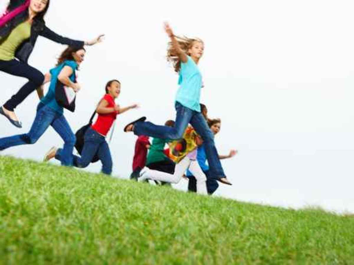 Young girls and boys jumping on the ground raising hands