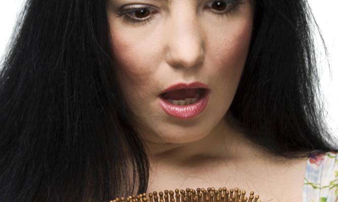 Shocked woman loss hair on hairbrush