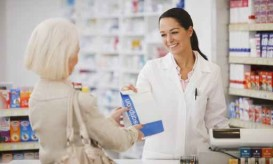 Pharmacist handing customer prescription in drug store