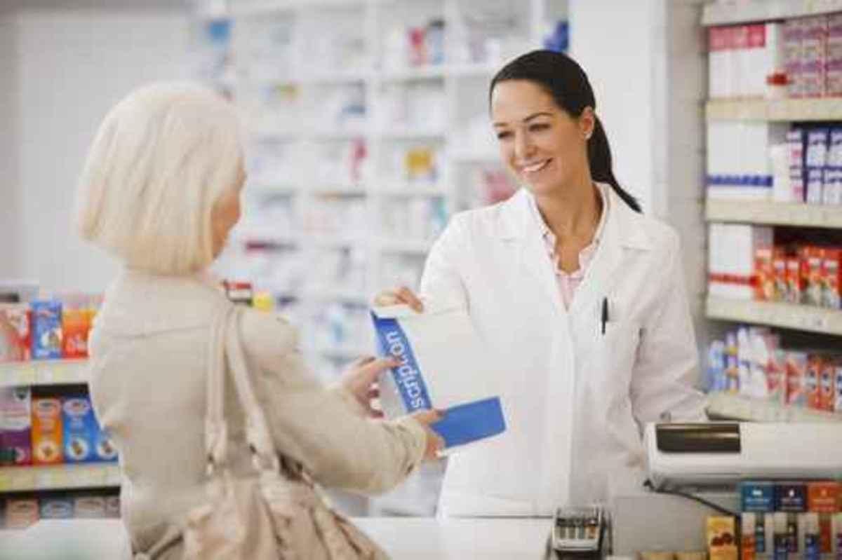 Pharmacist handing customer prescription in drug store