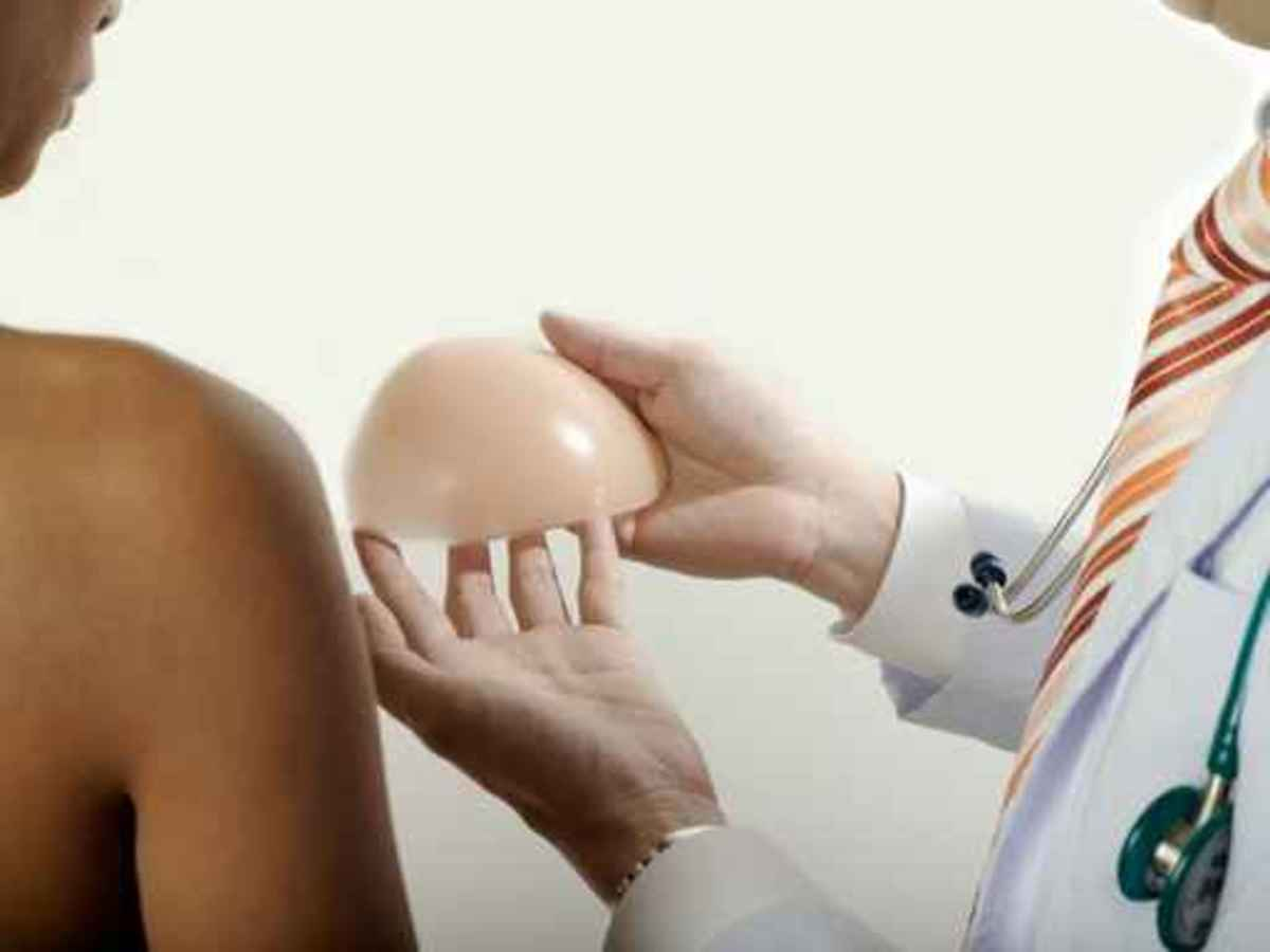 cosmetic surgeon showing patient a breast implant
