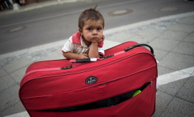 A migrant boy waits at his parents' suitcase as they leave the Berlin State Office for Health and Social Affairs with other newly arrived refugees who waited all day to apply for asylum in Berlin, August 10, 2015.  REUTERS/Stefanie Loos      TPX IMAGES OF THE DAY      - RTX1NTK2