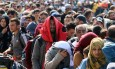 Migrants and refugees  waiting for buses after crossing  the border between Hungary and Austria in Nickelsdorf, Austria  70 kilometers (43 miles) southeast of Vienna, Sunday, Sept. 13, 2015. (AP Photo/Ronald Zak)