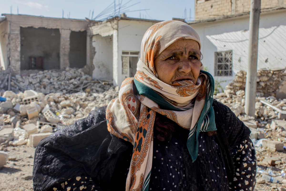 """Amneh from Al Mishlab, east of Raqqa city. She fled Al Mishlab with her family eight months ago. They moved five times before coming back as the front lines kept getting closer to their location. They came back to Al Mishlab to check their houses. Most of their houses are destroyed. She is standing in front of her grandchild house that was fully destroyed. She said """"we will try to rebuild our houses but there is still no services in the area yet."""""""
