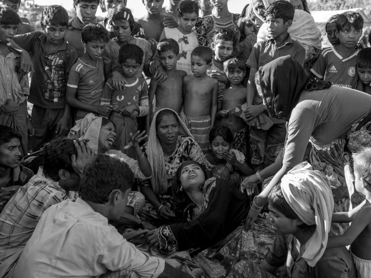 Relatives of Amina Khatun, a 60-year-old Rohingya refugee who died from complications related to starvation, mourn next to her body before her burial in the Balukhali refugee camp.