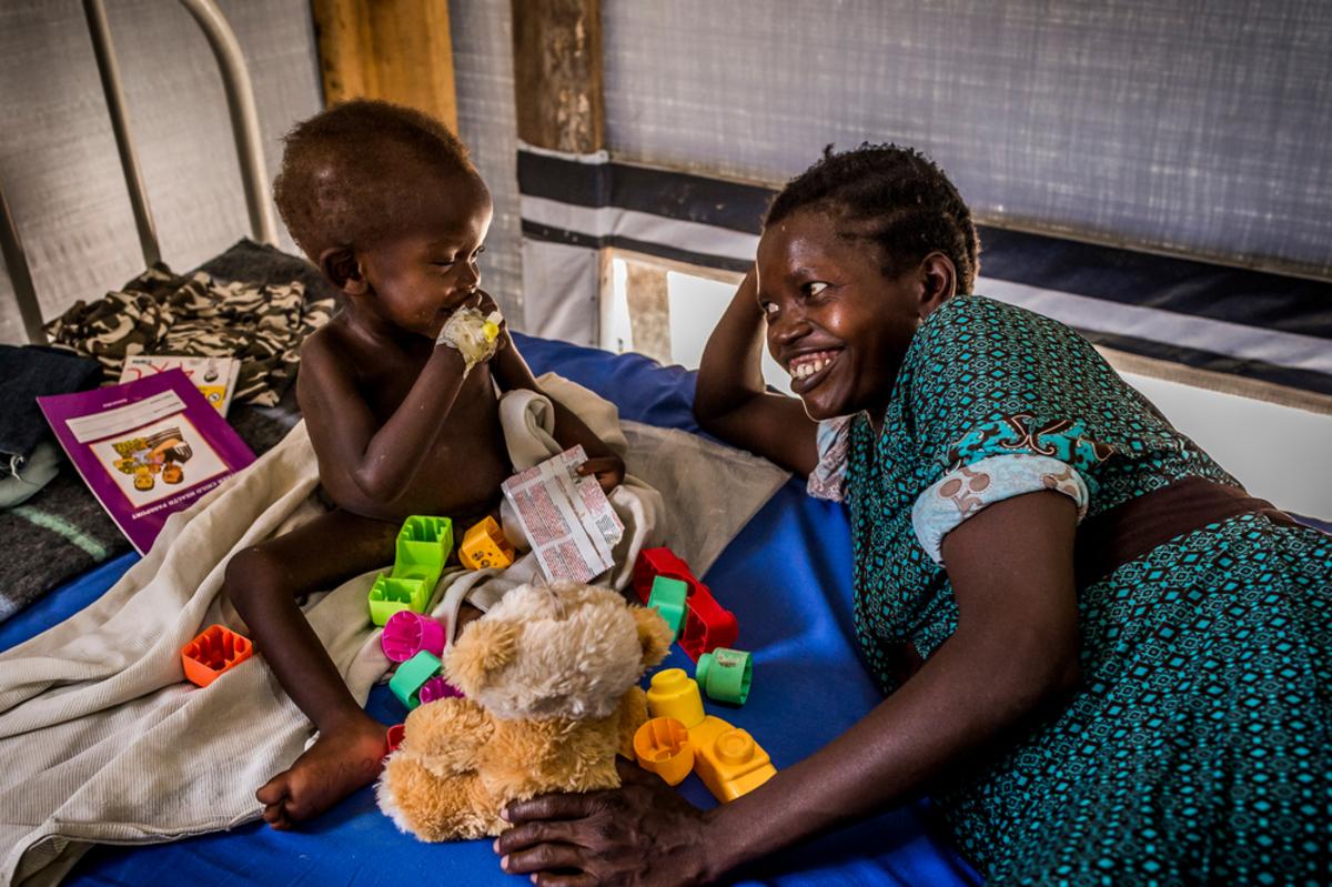 In Patient Department of Bidibidi, MSF Health Center. A young boy suffering from malnutrition with his mother. In Patient Department of Bidibidi, MSF Centre de Santé. Un jeune garçon souffrant de malnutrition avec sa mère.