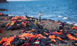 Lesbos, Greece - October 25, 2015: With hundreds of thousands of migrants arriving by boat on the Greek island of Lesbos, life jackets and deflated rubber boats lay scattered along the coastline. Here three men sort through the debris.