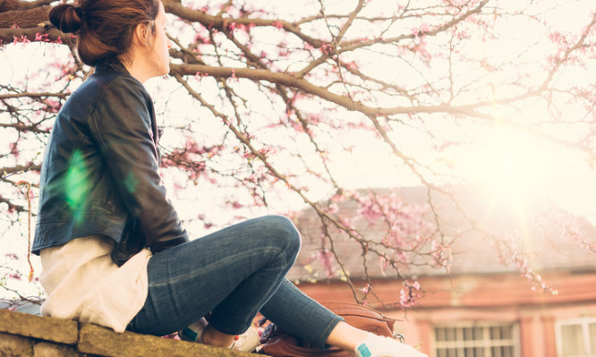 Thoughtful woman resting near the cherry blossom