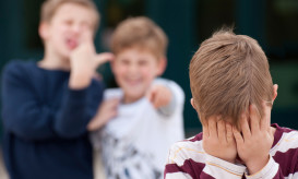 An upset elementary school boy hides his face while being bullied by two other boys.  Shot in front of their elementary school.
