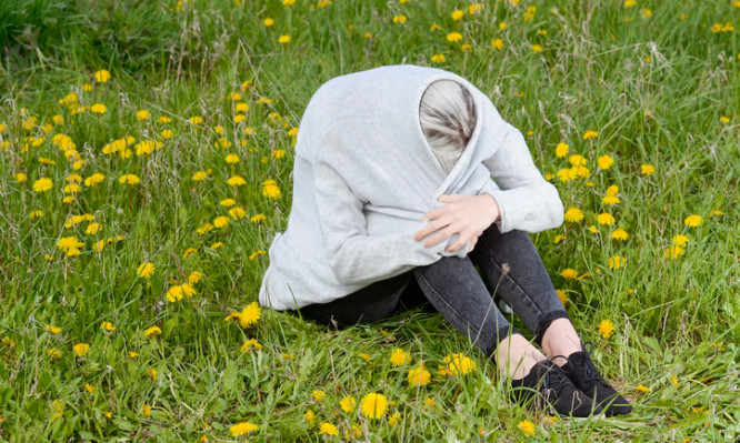 frustrated young woman sitting on flower meadow