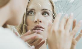 Face of schizophrenic woman reflected in broken mirror