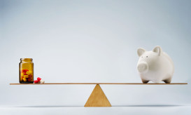 Piggy bank balancing on seesaw over a bottle of pills
