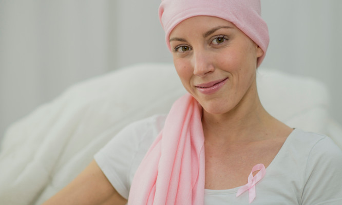 A woman with breast cancer is wearing a pink ribbon on her blouse and has a pink bandana around her head. She is hopeful and is smiling while looking at the camera.