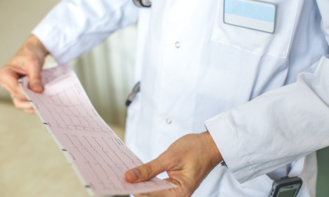 doctor interprets the results of his patient. Doctor is holding and looking at electrocardiogram paper.