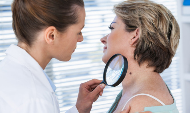 Dermatologist examining mole with magnifying glass in clinic