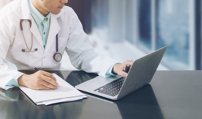 Male doctor working on desk with laptop computer and paperwork on his desk. Medical concept by doctor on computer in office with stethoscope over hospital background.