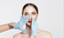 Rhinoplasty. wish to be beautiful need for beauty. Closeup portrait doctor hands with gloves  touching woman face nose want to change her form do plastic surgery.  cropped image horizontal studio shot