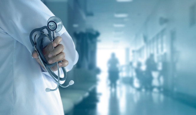 Doctor with stethoscope in hand on hospital background