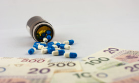 Pills spill out of the overturned bottle in the direction of Polish zlotys banknotes as a symbol of expensive medical care or drug addiction.