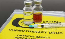 Vials of chemo drugs and a syring resting on chemotherapy drug bag.