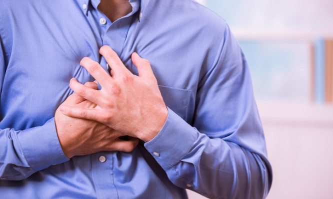 Mid-adult man clutching his chest in pain with a possible heart attack.  He wears a blue, button down dress shirt.  Heart disease.