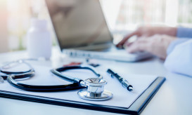 Stethoscope with clipboard and Laptop on desk Doctor working in hospital writing a prescription  Healthcare and medical concept test results in background vintage color selective focus.