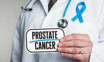Doctor with stethoscope in white lab coat holding sign reading prostate cancer