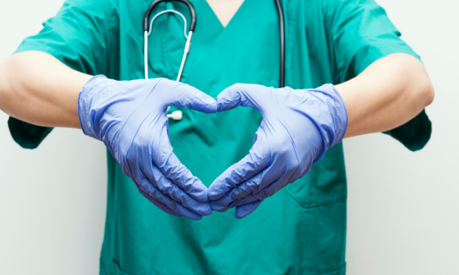 Doctor making heart shape with hands, vertical