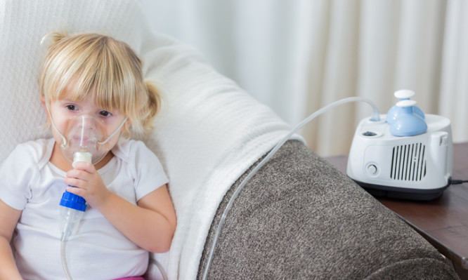 Caucasian preschool age girl on sofa receives breathing treatment. Her blond hair is in pigtails.