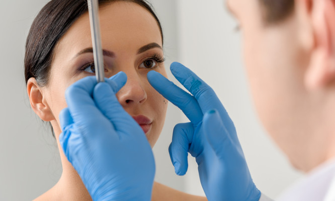 Focus on doctor hands showing where correct nose of calm woman. She watching at therapeutic