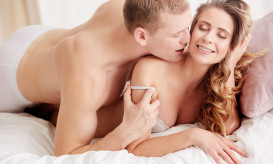 Man whispering sexy exciting words in woman's ear during foreplay