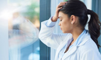 Shot of a young female doctor looking stressed out while standing at a window in a hospital