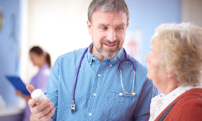 A mature male doctor is chatting to his female senior patient. He is dressed in an open neck shirt , and a beard and is holding a bottle of pills advising the patient. He is smiling and re-assuring. They are both standing in the foreground .In the background a female nurse can be seen defocussed .
