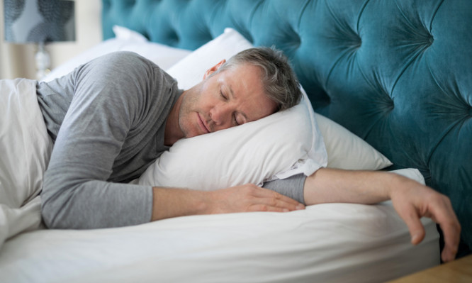 Man sleeping on bed in bedroom at home