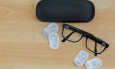 Spectacles with black frame, eye glasses case next to pairs of new breathable monthly disposable contact lenses made of silicone hydrogel on wooden background