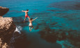Young active man and woman diving from high cliff into tropical island blue sea water